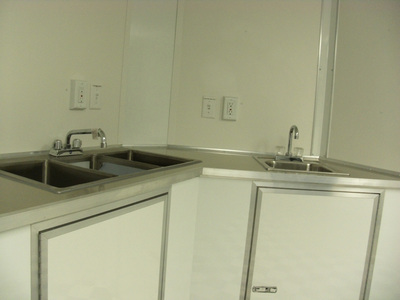 Closeup view of sinks and cabinets in Haulmark Transport with Concession Package.
