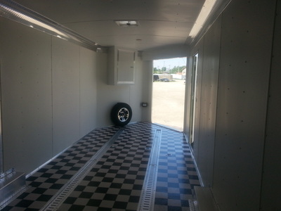 Interior shot of car hauler with black and white flooring, etrack, spare tire and mount, interior lighting and side front ramp