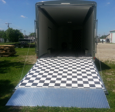 Exterior view of custom car hauler with ramp down showing black and white flooring and interior of hauler