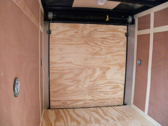 Interior shot of enclosed utility trailer with plywood floor, walls and ramp plus interior lighting