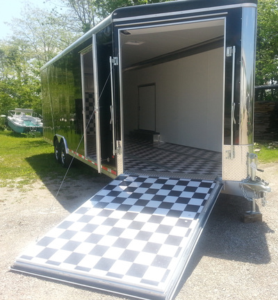 Exterior view of black car hauler with black and whit flooring, front ramp down