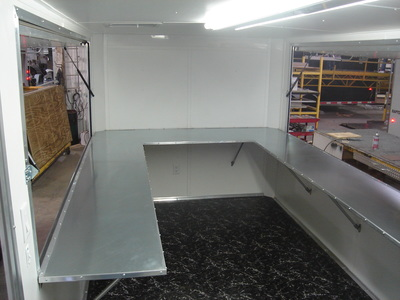 Interior shot of vending/concession trailer with rubberized flooring, white walls, fold down counters and utilty racks