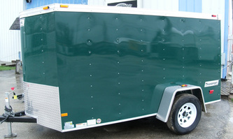Enclosed utility trailer in dark green with stoneguard