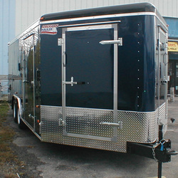 Black dual axle enclosed utility trailer with stoneguard and side door on the V Nose