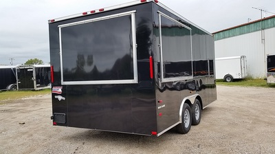 Exterior shot of American Hauler black dual axle vending/concession trailer with flip up windows and screwless exterior