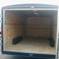 Interior view of enclosed utility trailer with plywood floor and walls plus roof vents