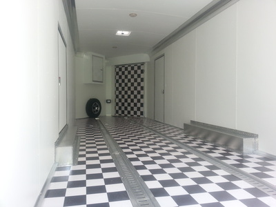 Interior shot of car hauler from rear ramp showing black and white flooring, e track, interior lighting, front ramp and spare tire with mount