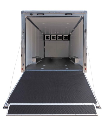 Interior shot of enclosed hauler with rubberized flooring, rear ramp, d rings  white walls and interior cabinets.