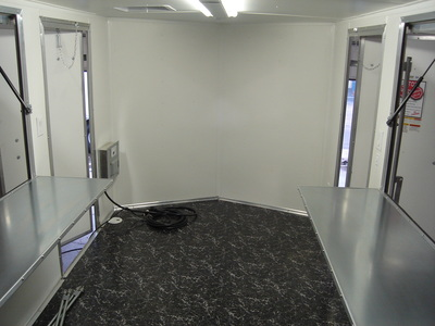Interior shot of v nose vending/concession trailer with rubberized flooring, white walls, interior power, folddown counters and flip up windows.