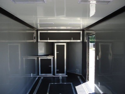Closer shot, Interior of Bonnie's race track special trailer with custome cabinets, white walls, rubberized coin flooring, e track, interior lighting and rear ramp